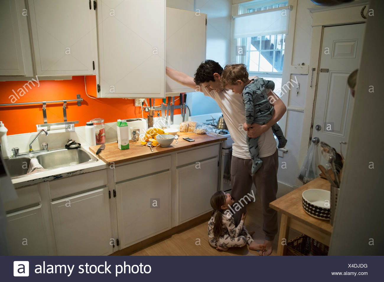 Father and children in pajamas in kitchen - Stock Image