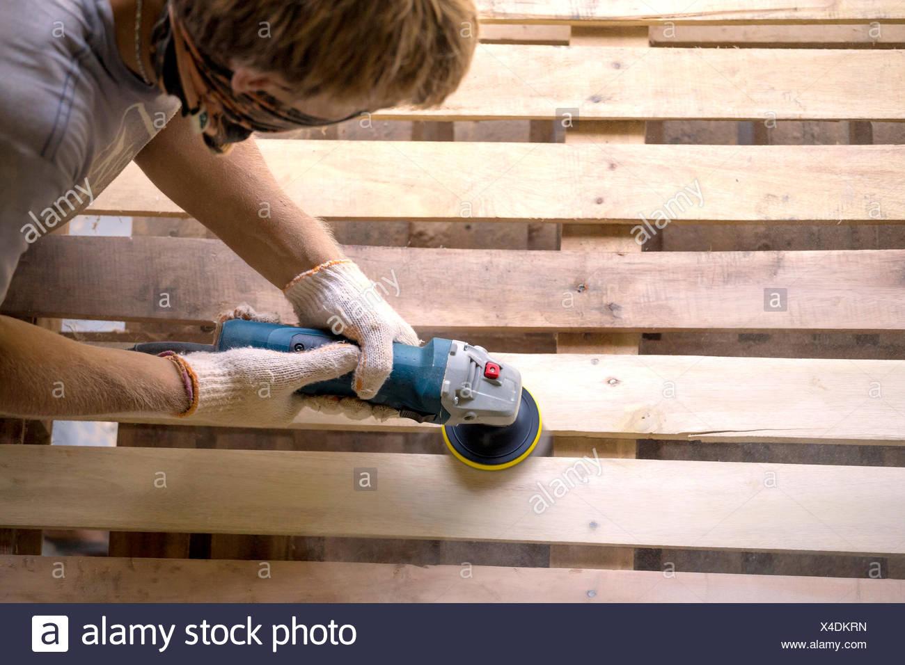 Man sanding pallet with a random orbital sander - Stock Image