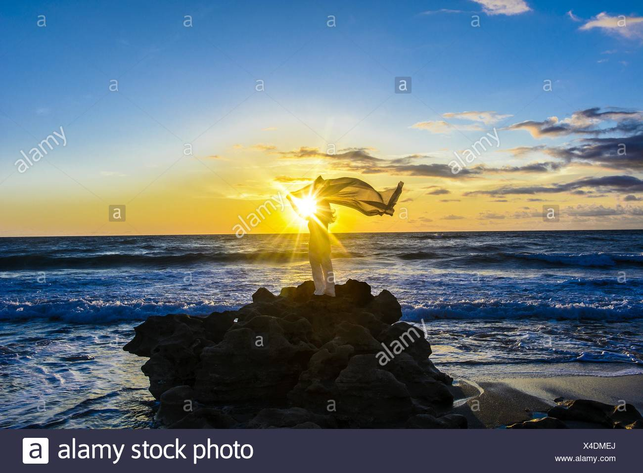 Woman With Sarong Blowing By Wind Standing On Rock In Sea Against Sky Stock Photo