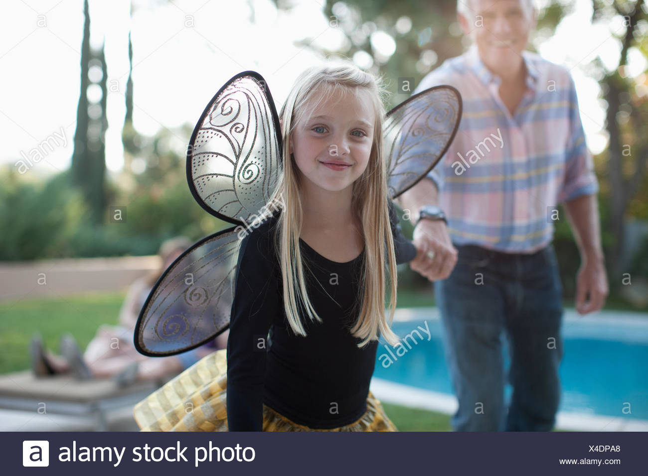 Girl in fairy wings pulling grandfather along - Stock Image
