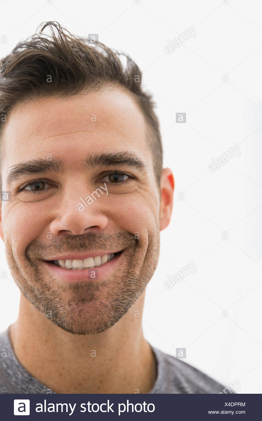 Close up portrait of smiling brunette man - Stock Image