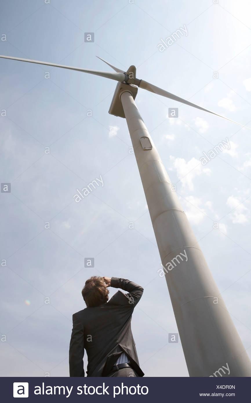 Businessman looking up at wind turbine - Stock Image