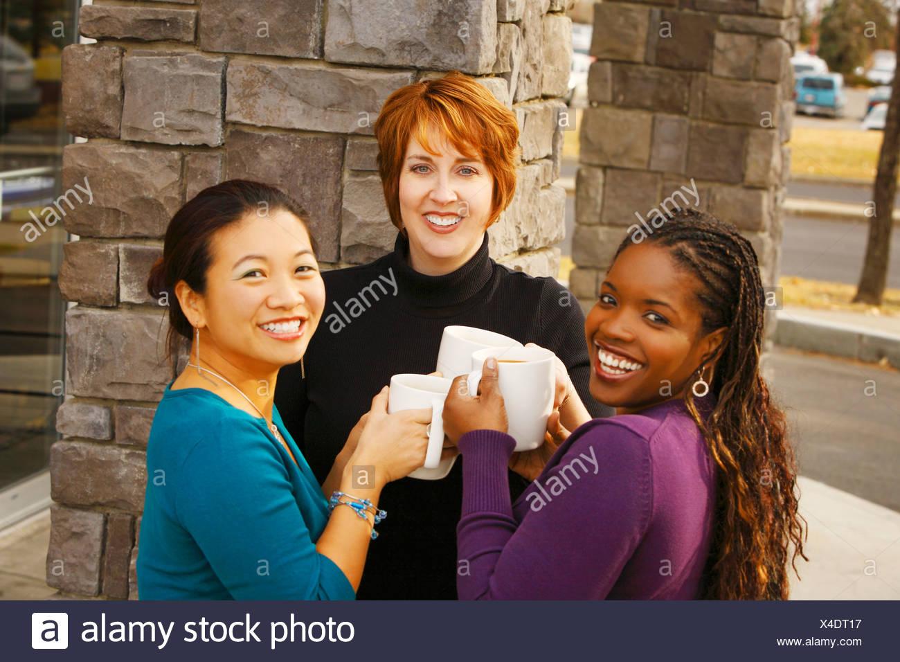 Three women celebrating together - Stock Image