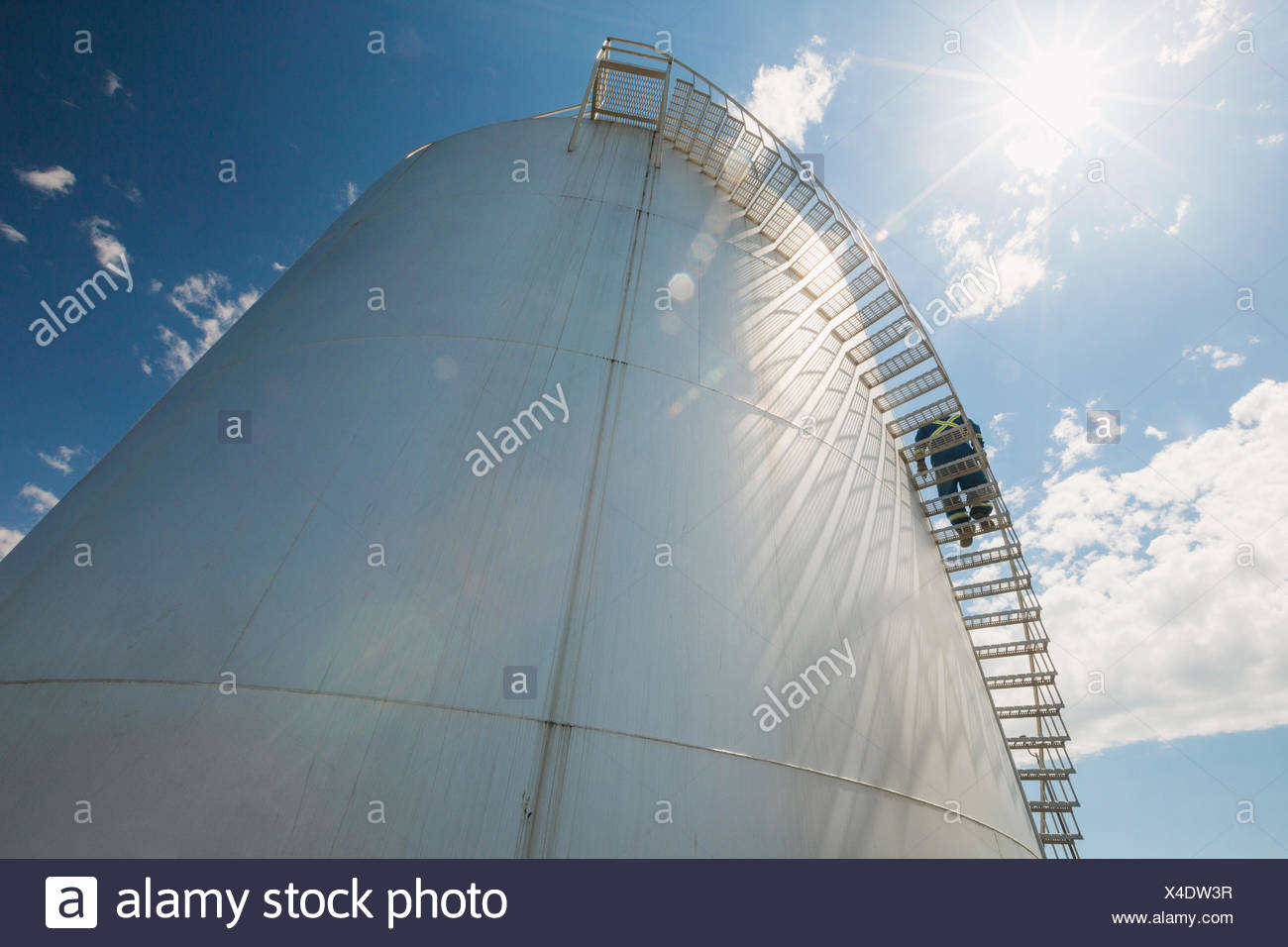 Worker descending spiral stairs of gas tower - Stock Image