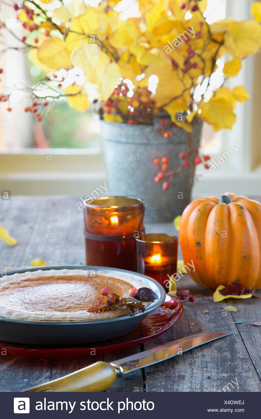 Autumn decorations and pumpkin pie on wood table - Stock Image