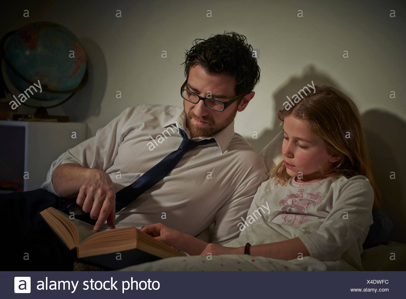 Businessman reading storybook to daughter at bedtime - Stock Image