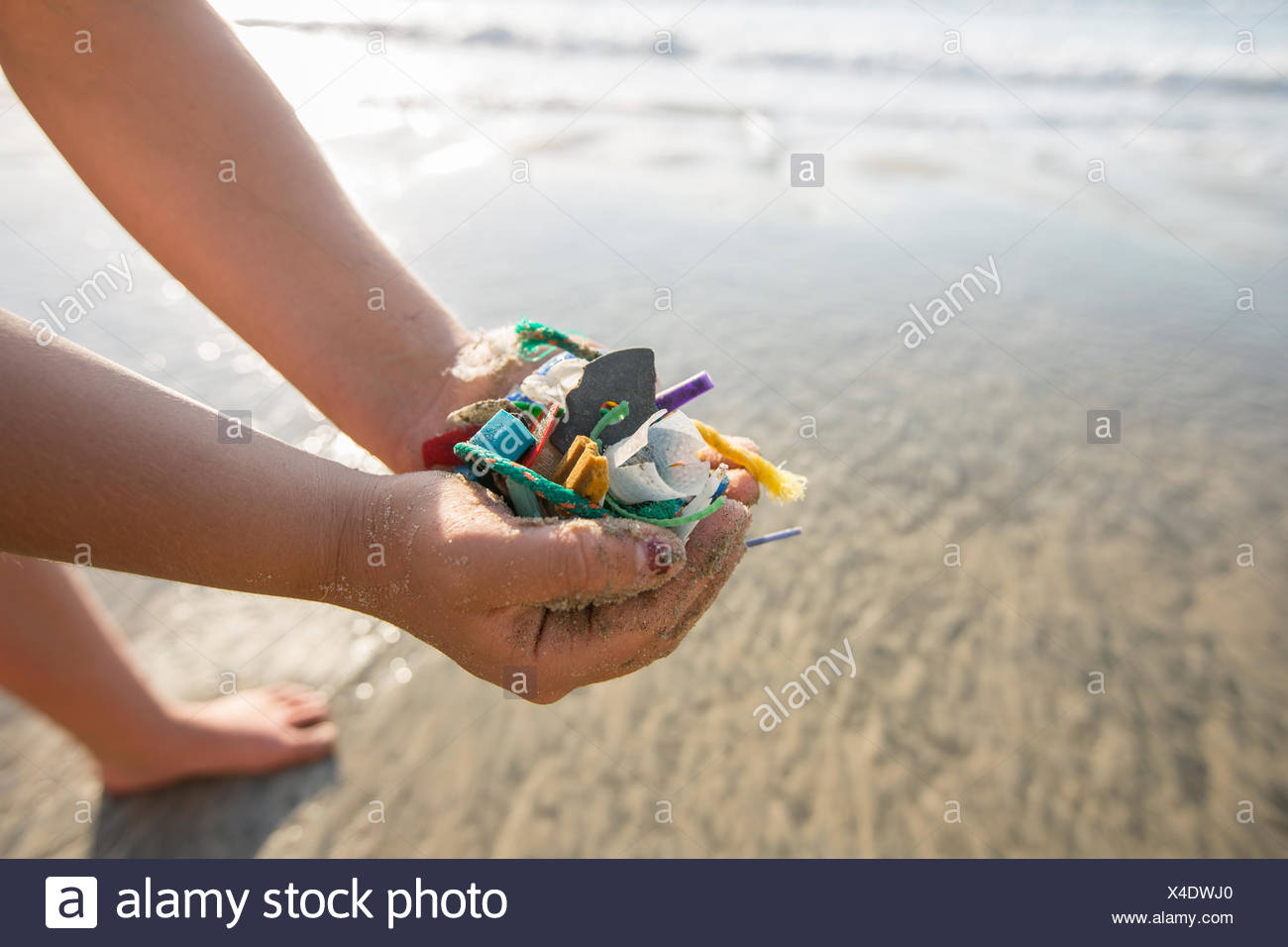 Close up of hands of girl holding plastic trash picked up at Torrey Pines State Beach in San Diego,California,USA - Stock Image