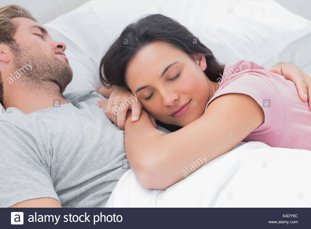 Woman sleeping on her husbands chest - Stock Image