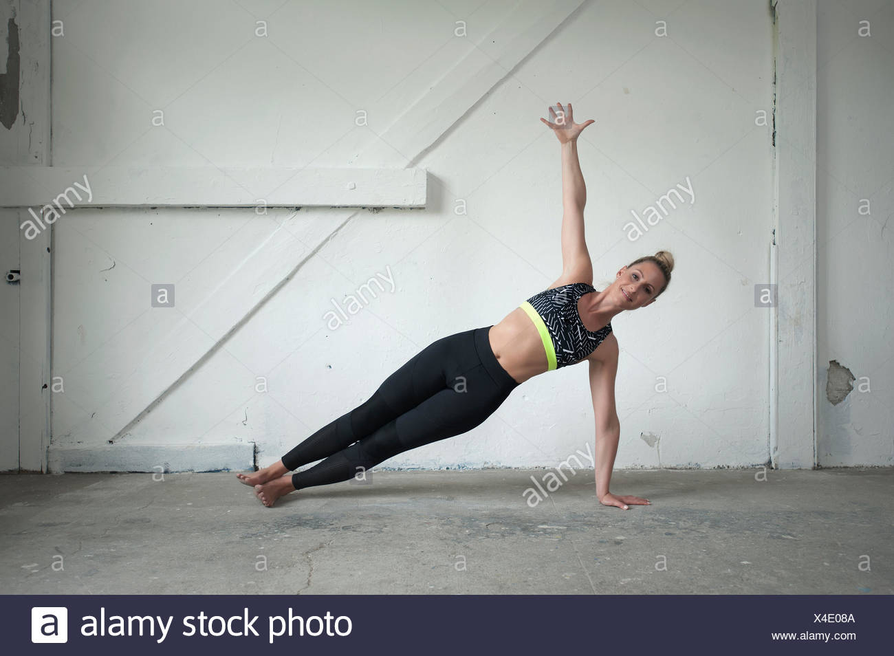 Mid adult woman practicing side plank pose in yoga studio, Munich, Bavaria, Germany - Stock Image