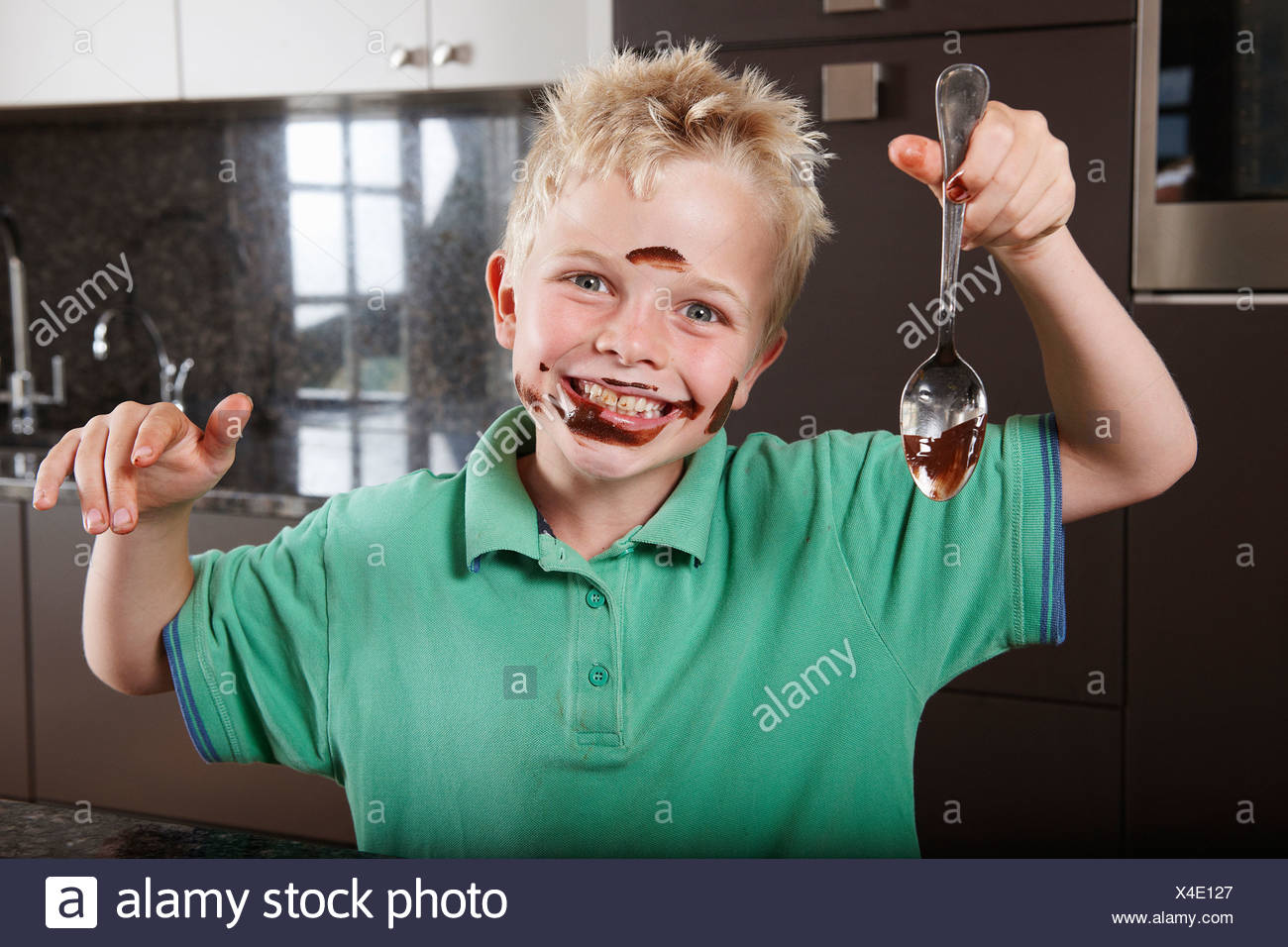Boy in kitchen with cake mix on his face - Stock Image