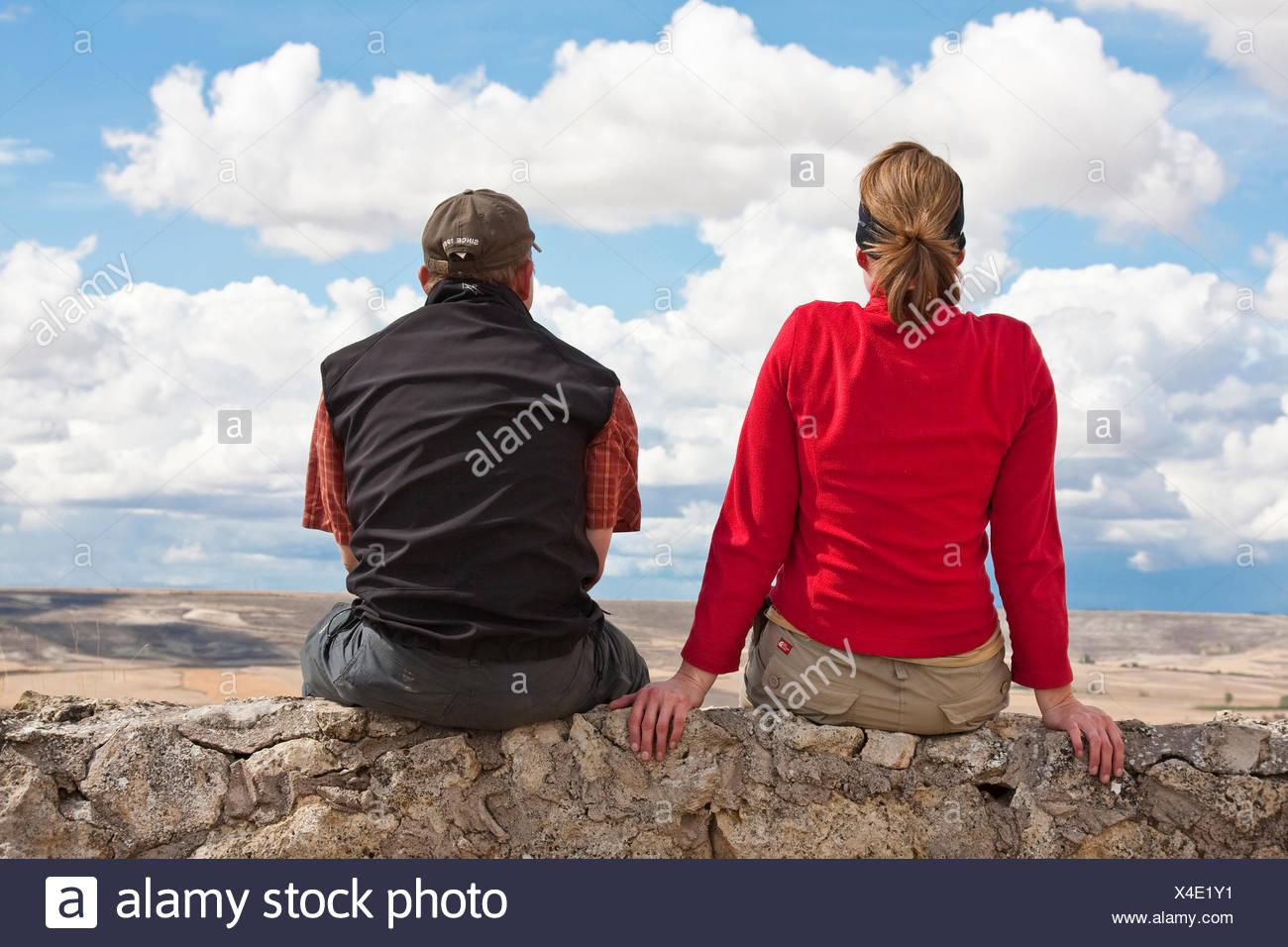 two pilgrims on Camino de Santiago sitting on a wall looking back to Castrojeriz, Spain, Kastilien & Leon, Burgos - Stock Image