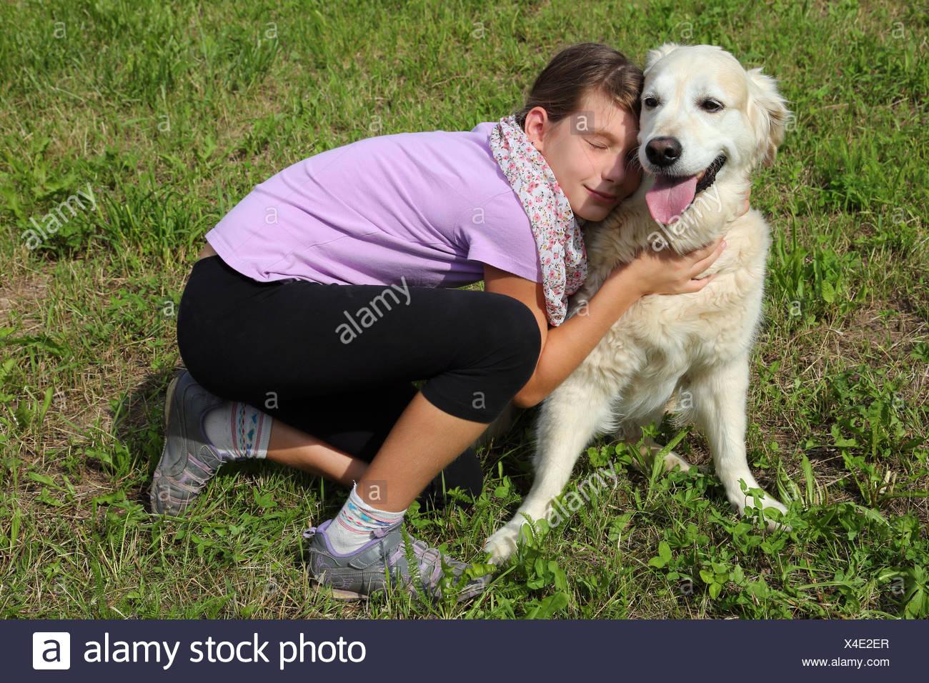 Ein Kind schmust mit einem Hund Stock Photo
