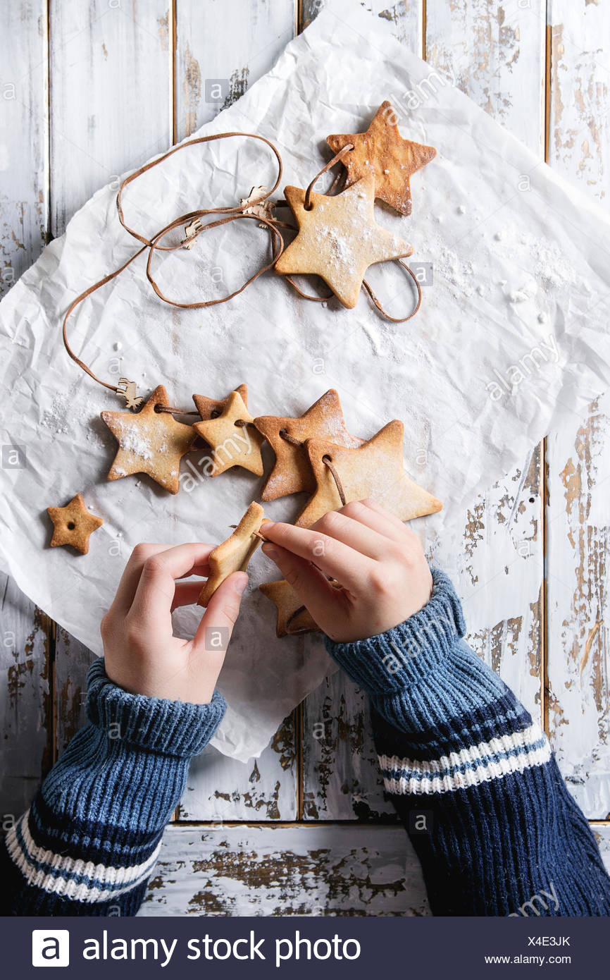 Child hands make garland of homemade shortbread star shape sugar cookies different size on thread on baking paper over white wooden plank table. Chris - Stock Image