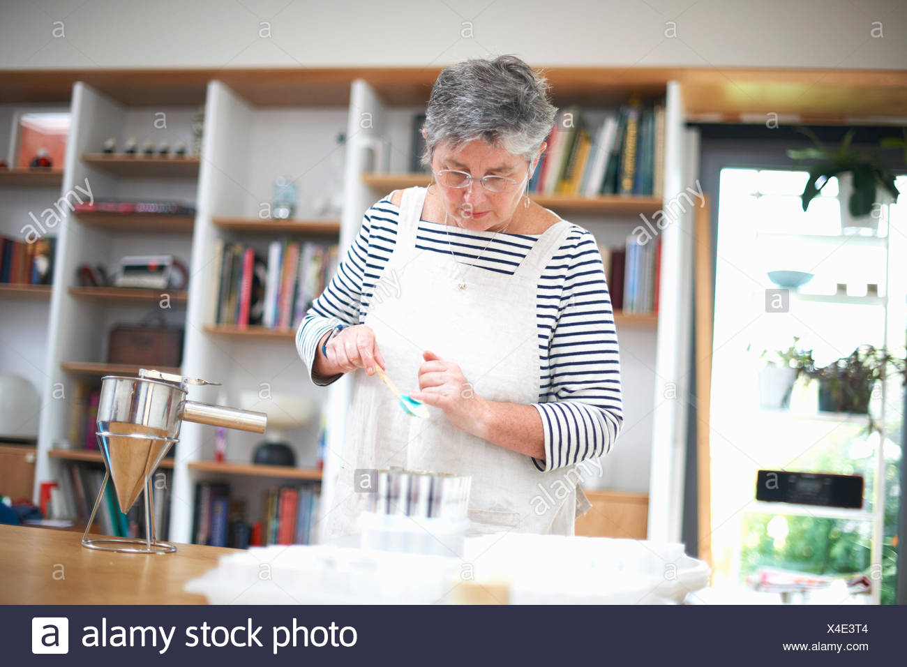 Senior woman tapping powder into containers - Stock Image