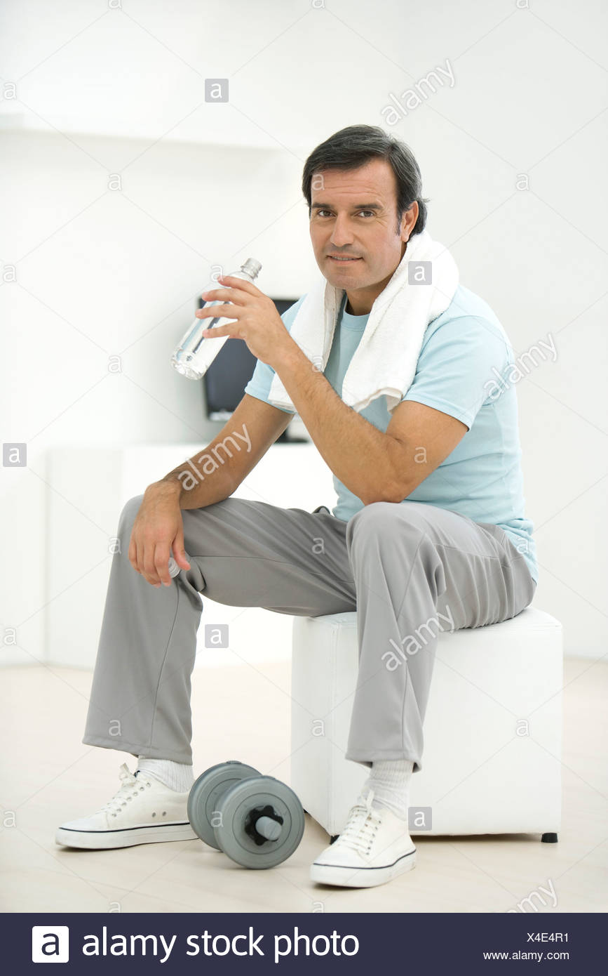 Man in sports clothing holding water bottle, dumbbell at his feet Stock Photo