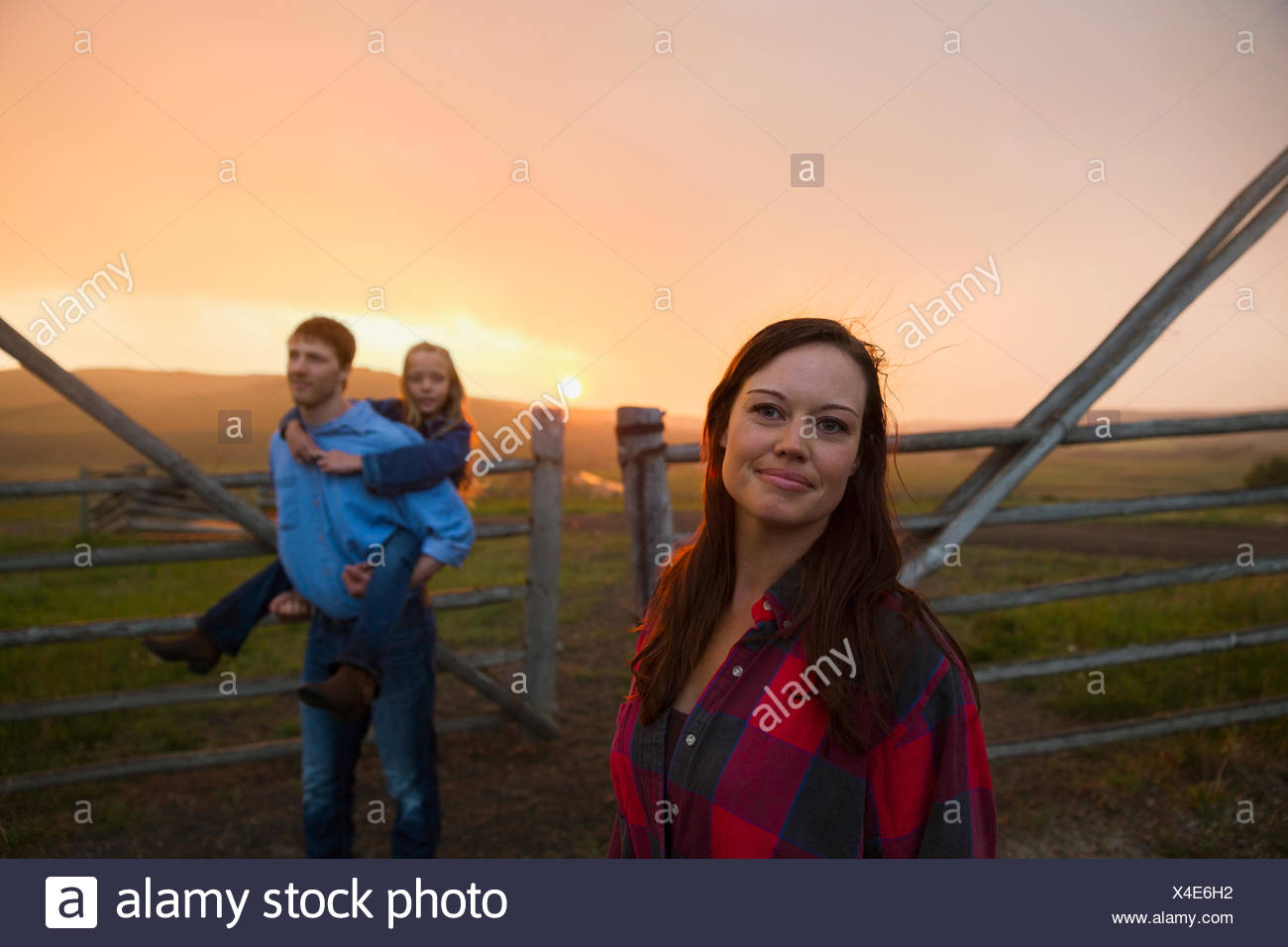 Woman with family in pasture at sunset - Stock Image