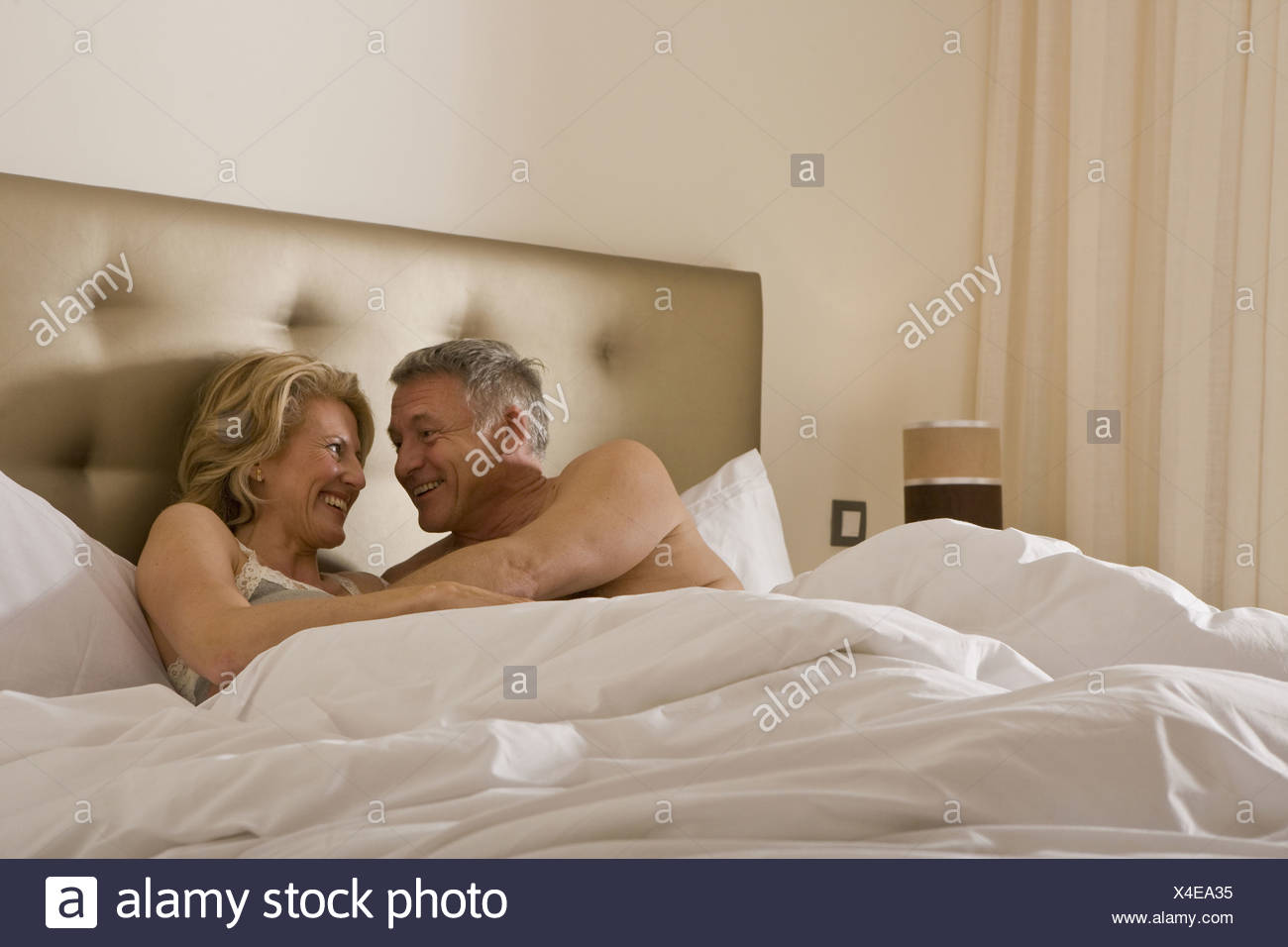 Mature couple embracing tenderly in bed - Stock Image