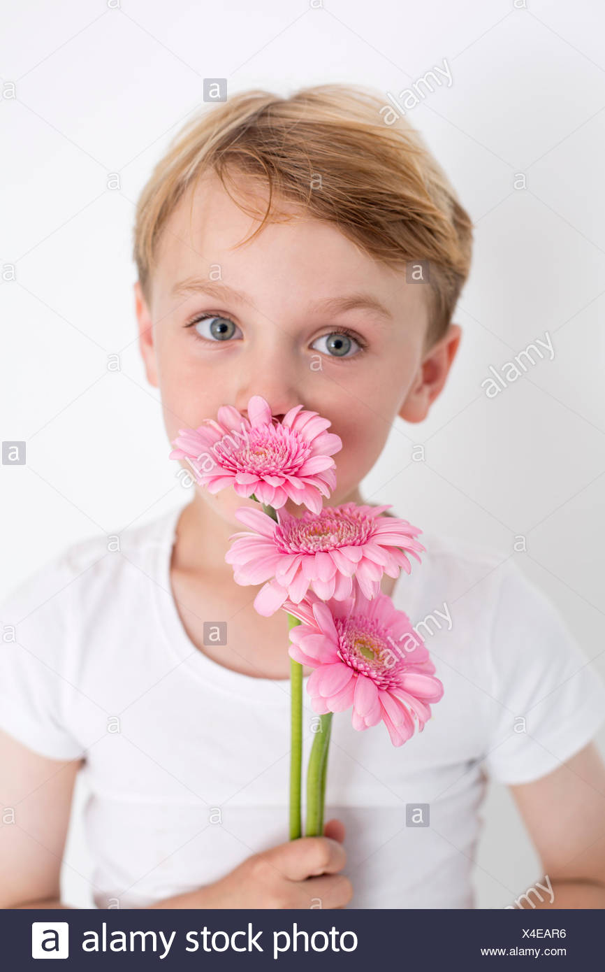 Young boy posing for a picture in a photographers studio, holding a bunch of flowers. - Stock Image