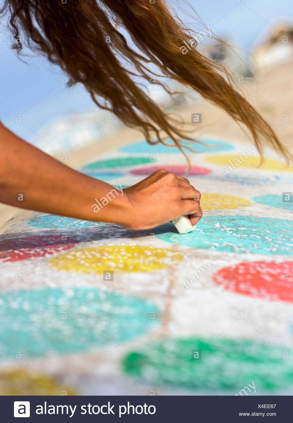 A female surfer waxes her longboard surfboard on a windy day in Newport Beach, Calif. - Stock Image