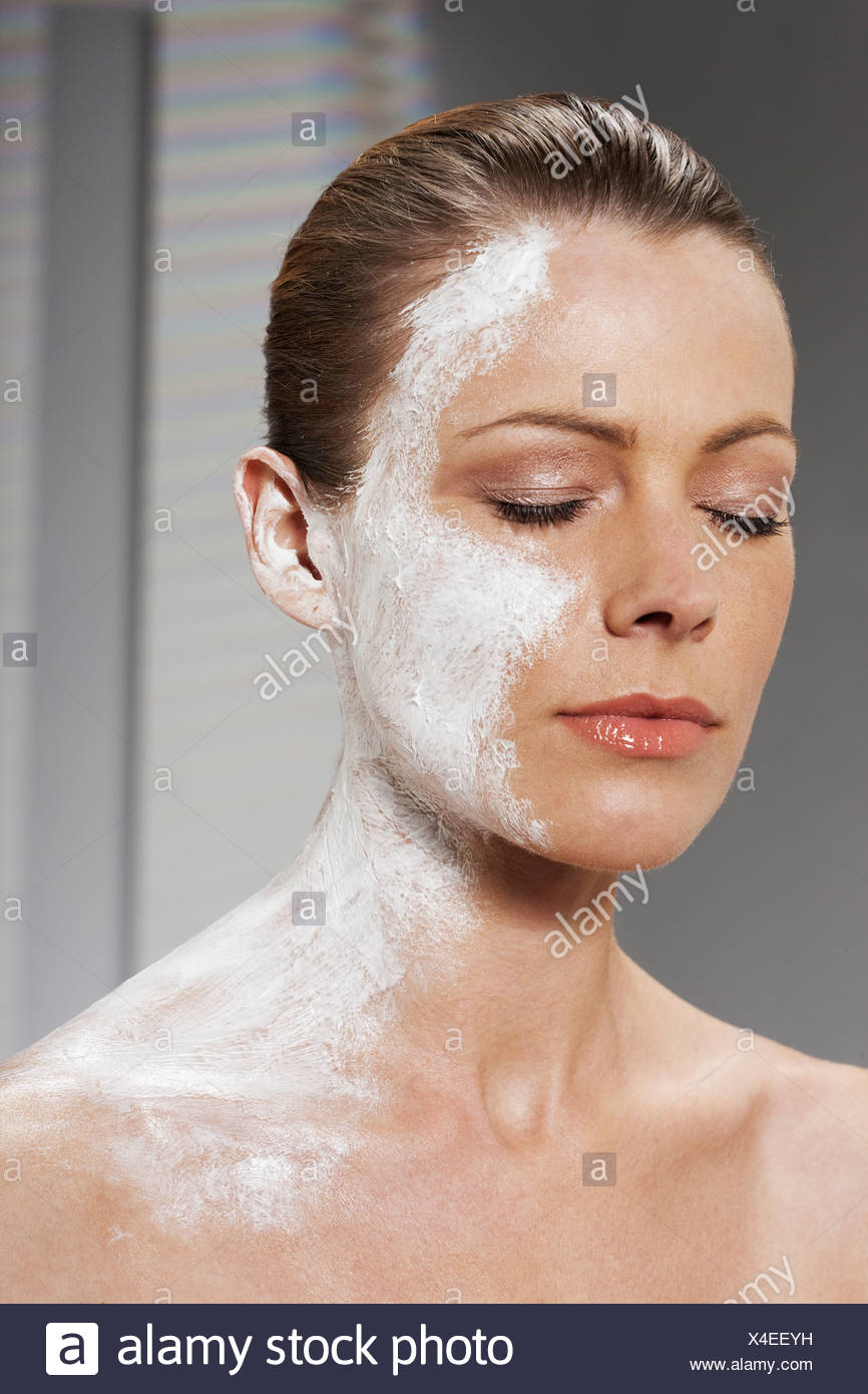 Woman with moisturizer on face and neck - Stock Image