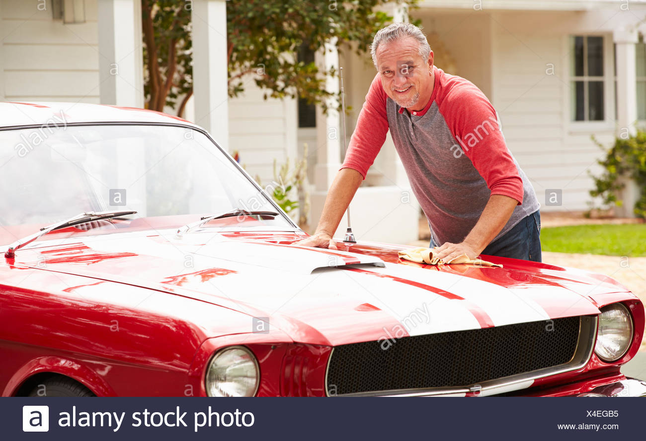 Retired Senior Man Cleaning Restored Classic Car - Stock Image
