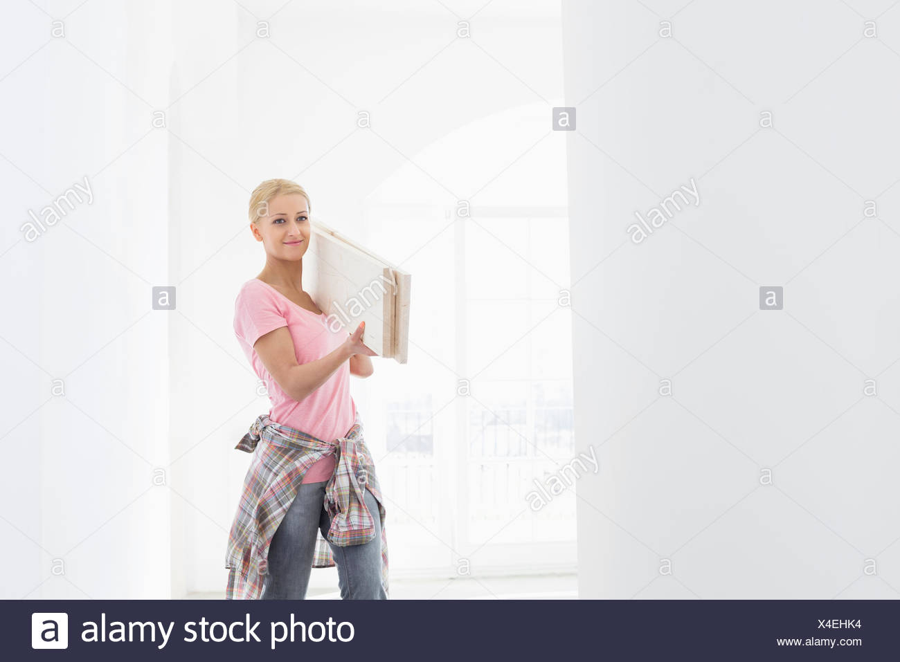 Woman carrying wooden planks on shoulder - Stock Image