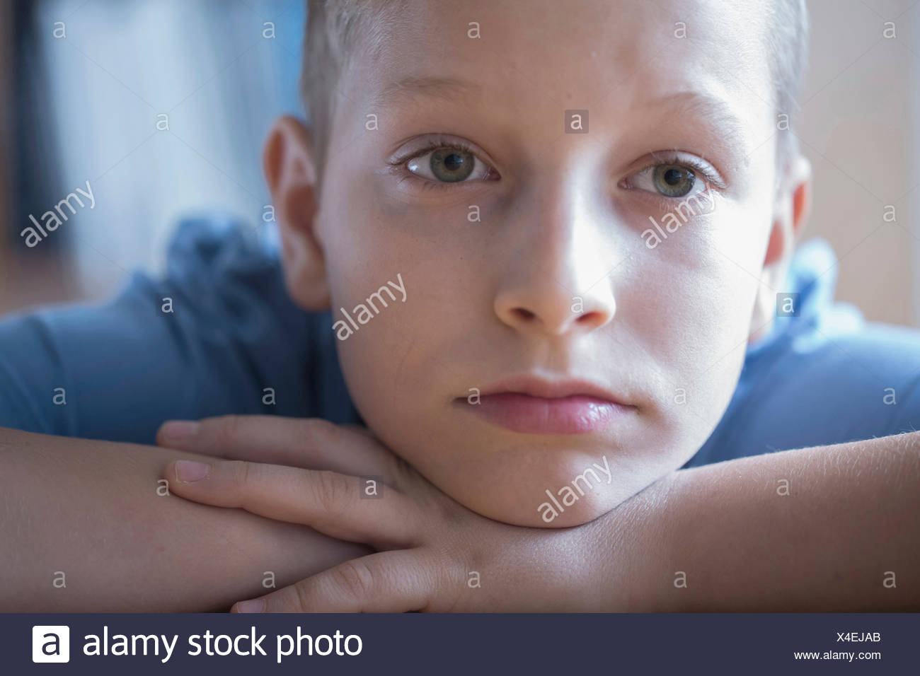 Sad boy resting head on arms, Freiburg im Breisgau, Baden-Württemberg, Germany - Stock Image