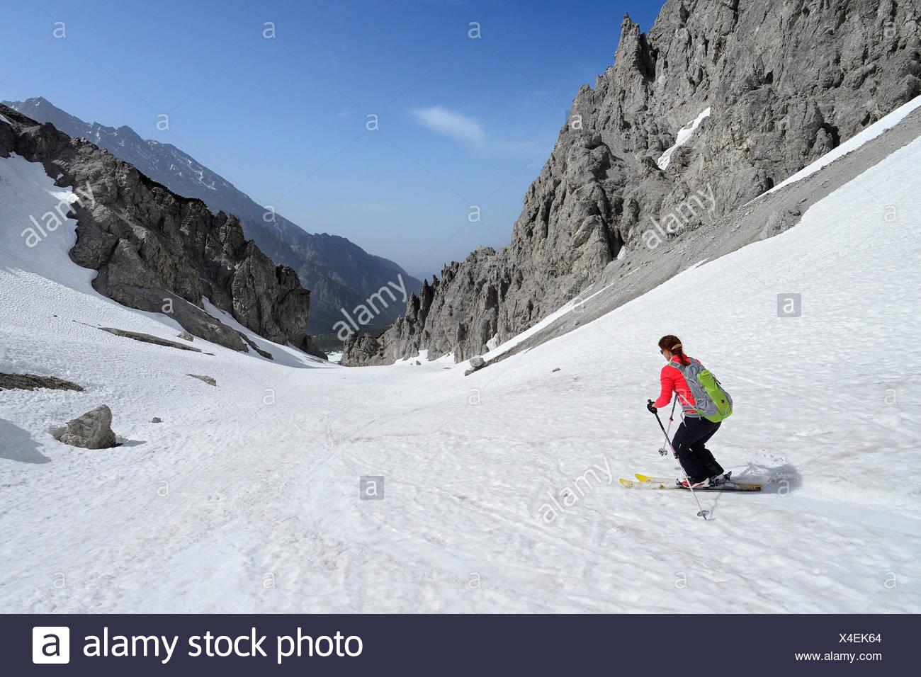 Female backcountry skier downhill skiing through Loferer Seilergraben, Berchtesgaden Alps, Berchtesgaden National Park, Upper Ba - Stock Image