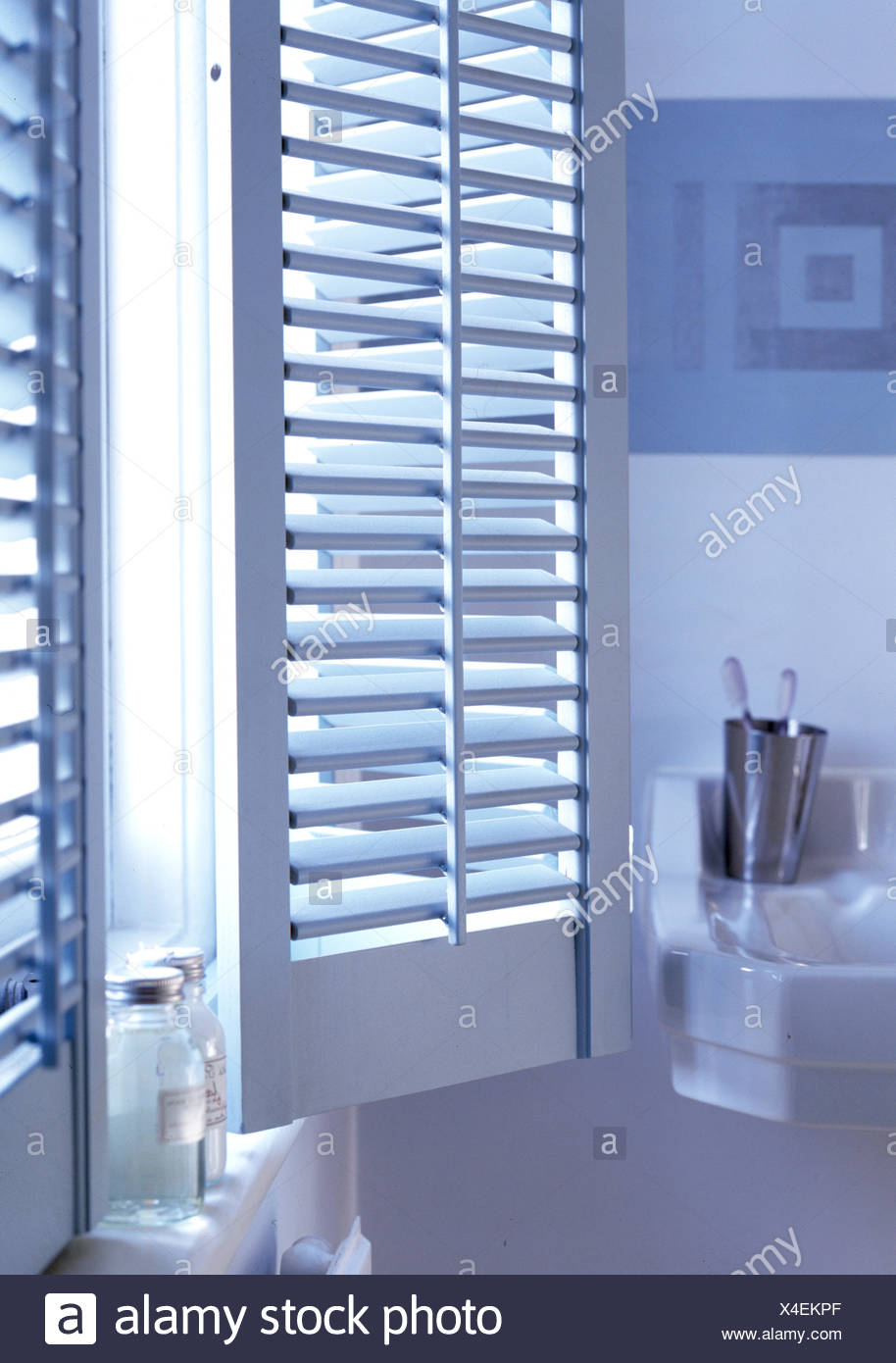 Plantation Shutters On Window In Blue And White Bathroom Stock Photo