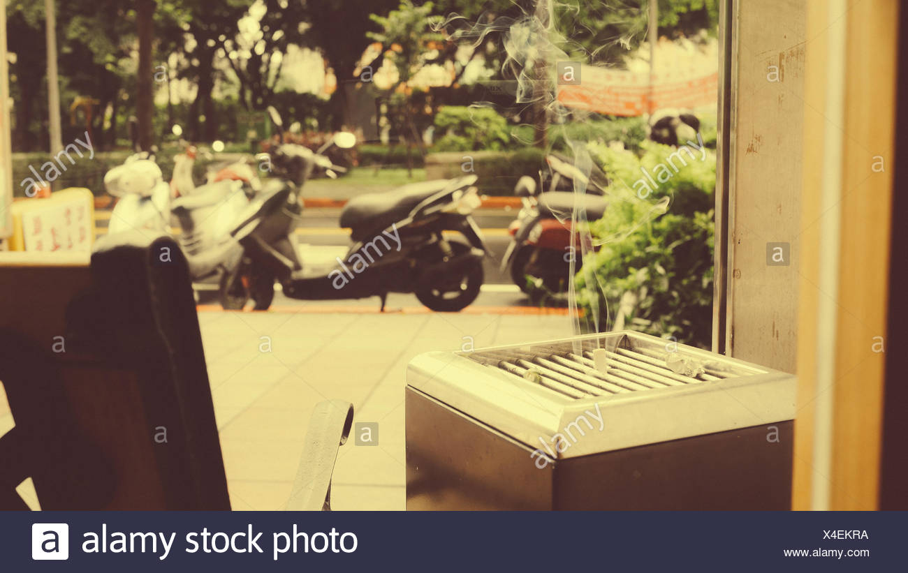 Smoke From Cigarette Receptacle Against Glass Window - Stock Image