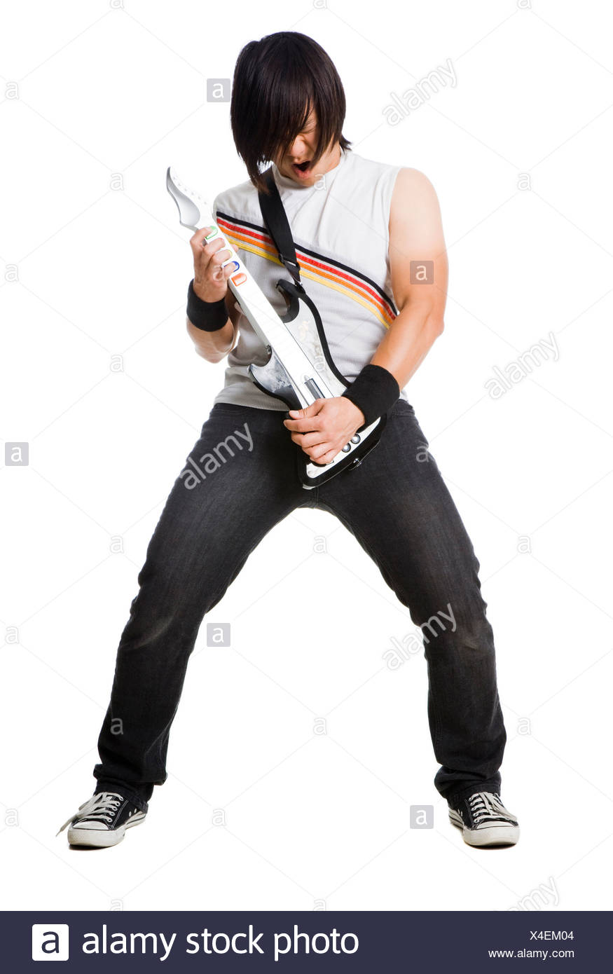 Young man playing guitar video game and screaming, studio shot - Stock Image