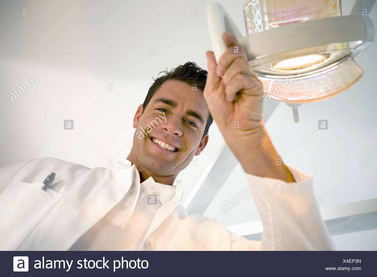 Male dentist smiling and adjusting dental light - Stock Image