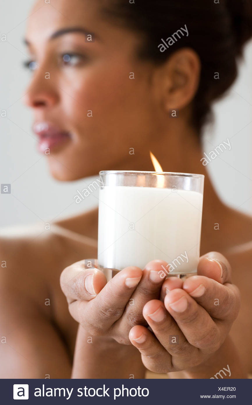 A woman holding a candle - Stock Image