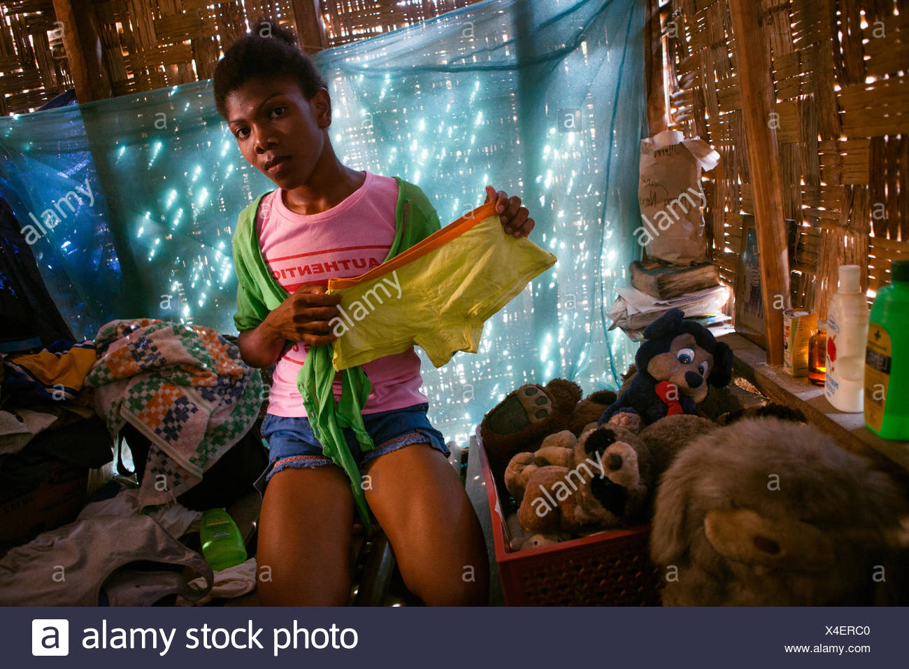 Alvina, formerly Alvin, a transgendered male Ayta holds up a pair of shorts. Access to mainstream media and the influence of popular transgendered people on television have helped the community become more accepting of their two transgendered members. - Stock Image