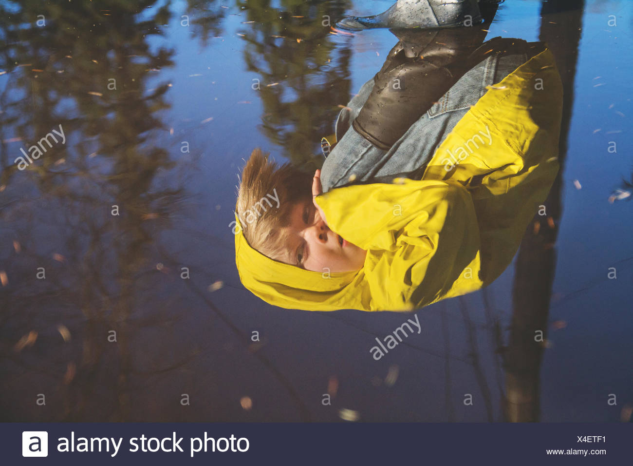 Reflection of boy in rain coat looking into puddle of water - Stock Image