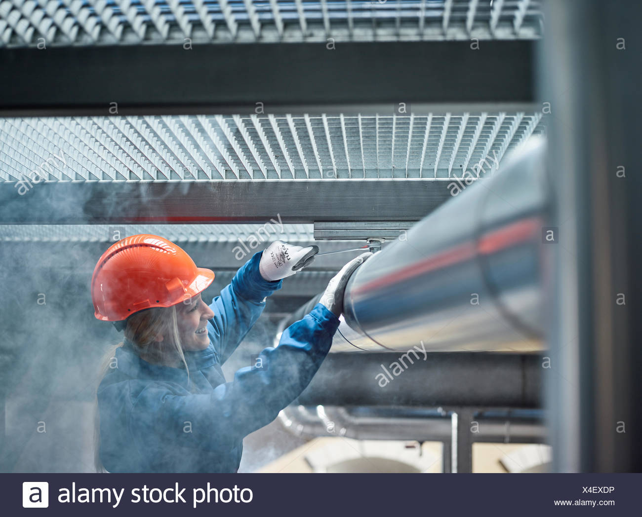 Technician, mechanic with orange helmet mounting a refrigeration line bracket, Austria - Stock Image