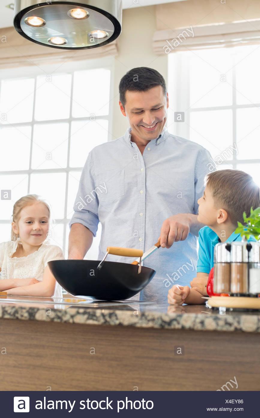 Happy man with children preparing food in kitchen - Stock Image