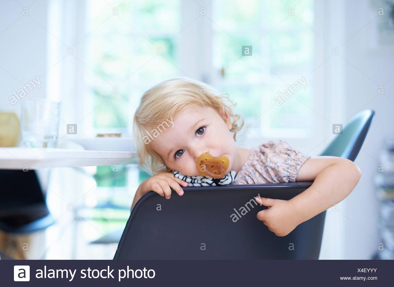 Portrait tired female toddler in living room - Stock Image