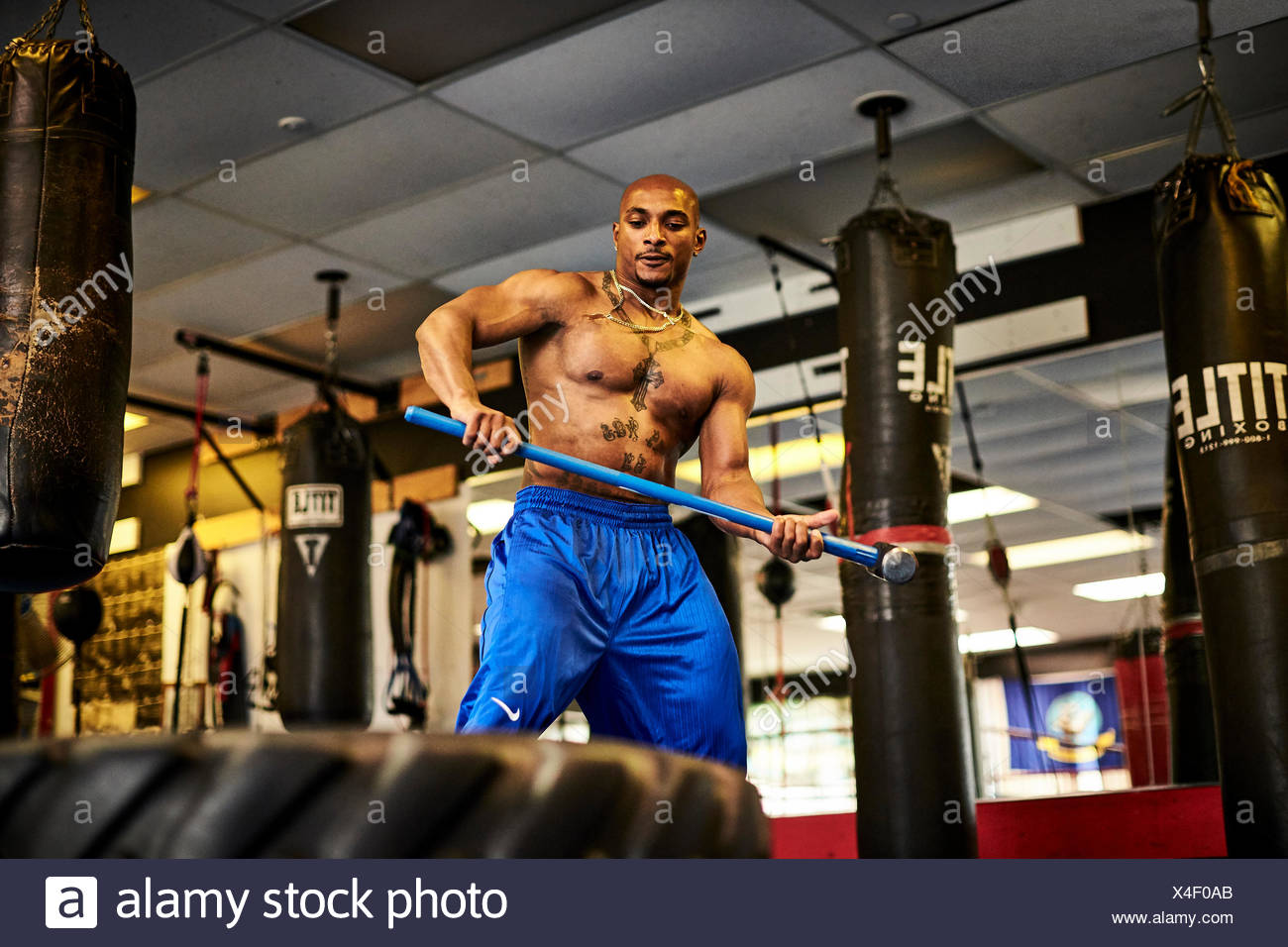 Shirtless athlete training in gym with tire and sledgehammer, Taunton, Massachusetts, USA - Stock Image
