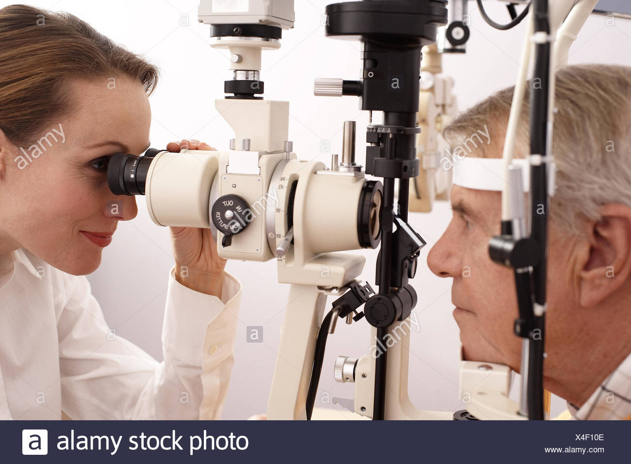 Optician performing eye exam on man - Stock Image