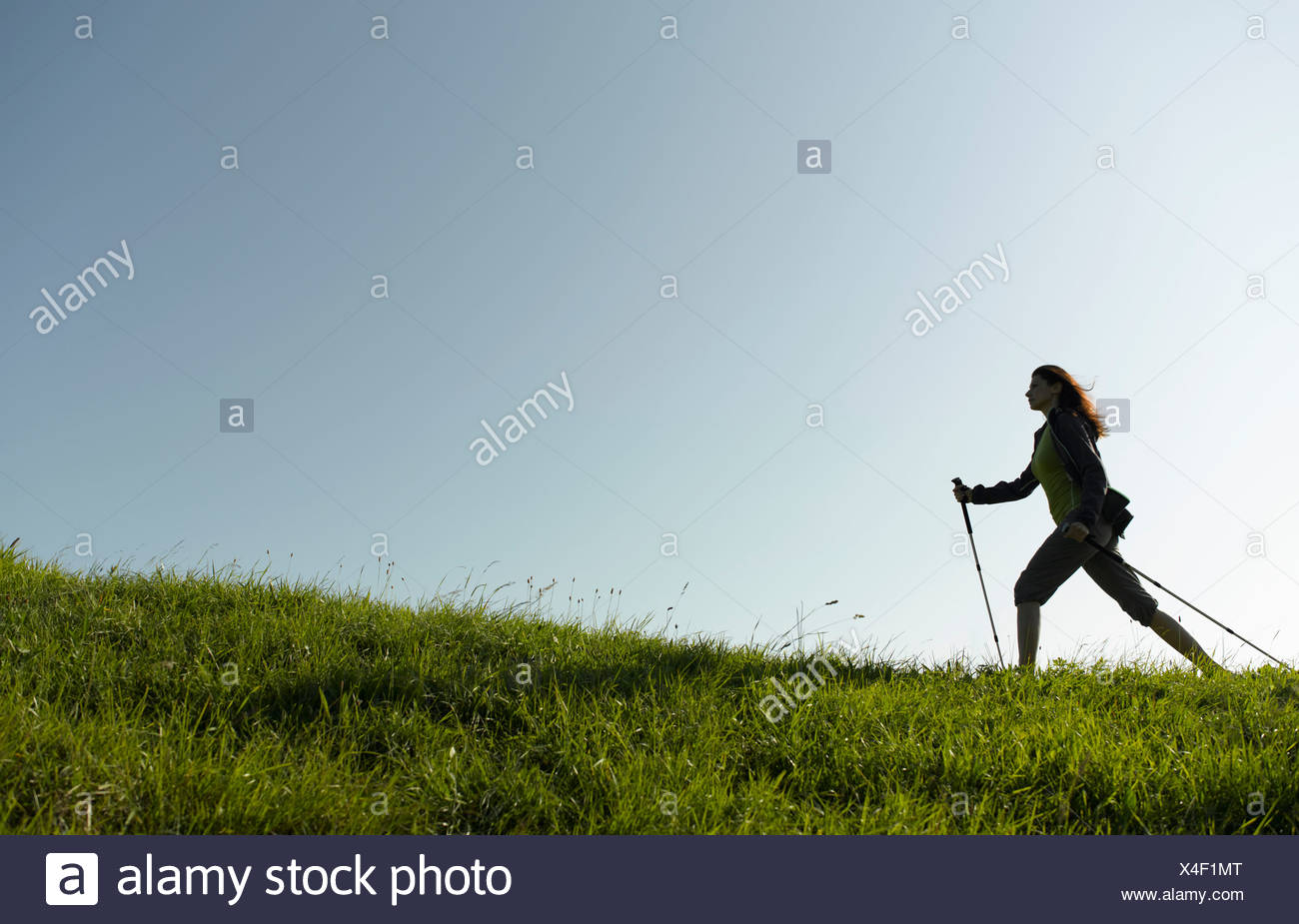 A woman out hiking, using walking poles - Stock Image