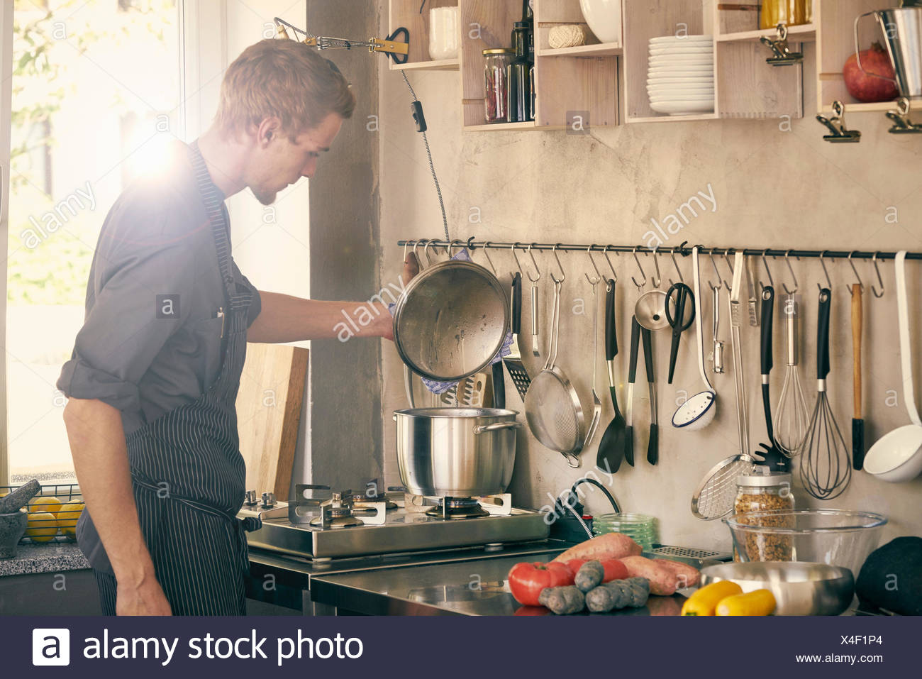 Chef cooking in commercial kitchen - Stock Image