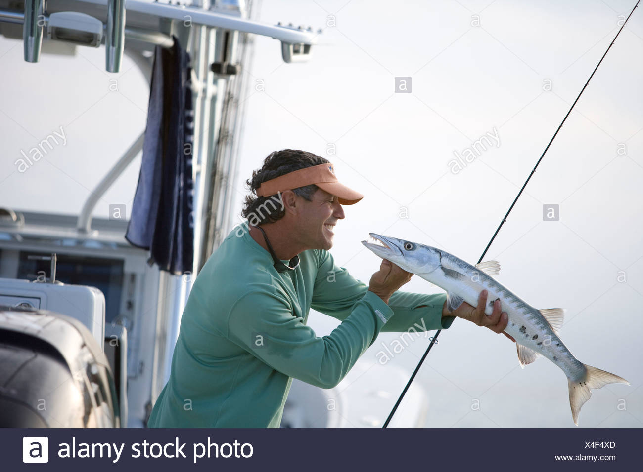 A fisherman smiles at the barracuda he has just caught. - Stock Image