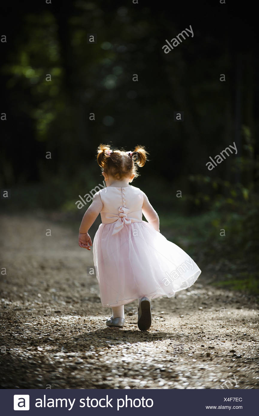 child running away from camera floaty special pink bridesmaid dress red hair pigtails Stock Photo