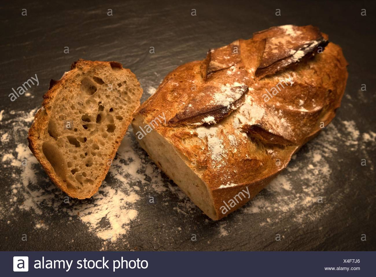 Loaf of bread with a slice - Stock Image