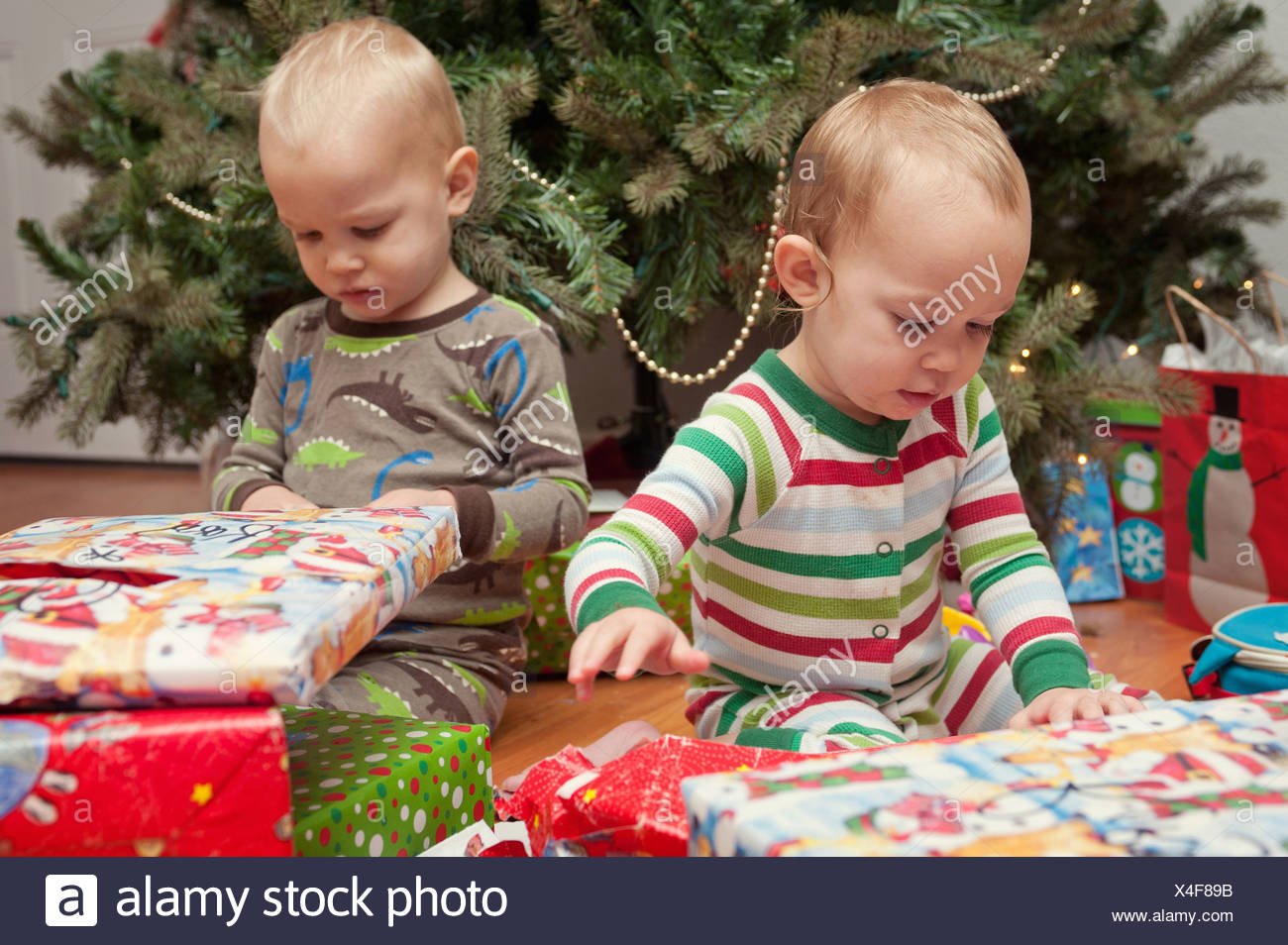 Christmas Presents For Brother.Brother And Sister Looking At Christmas Presents Stock Photo