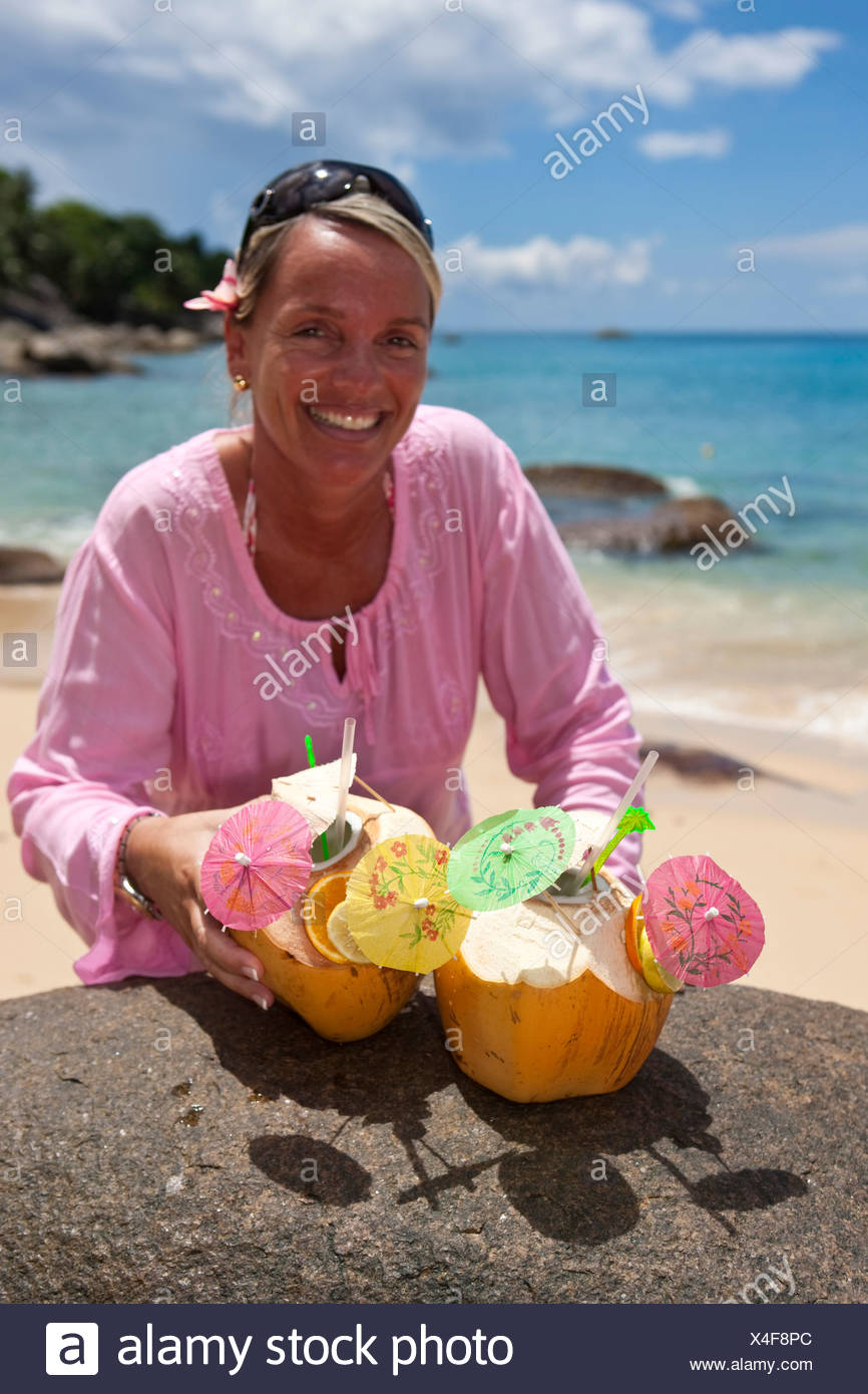 A woman in a pink tunic reaches for two decorated coconuts filled with drinks, island of Mahe, Seychelles, Indian Ocean, Africa - Stock Image