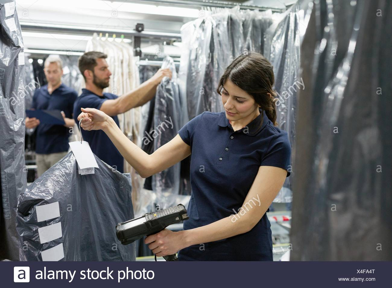 Three warehouse workers doing garment stock take in distribution warehouse - Stock Image