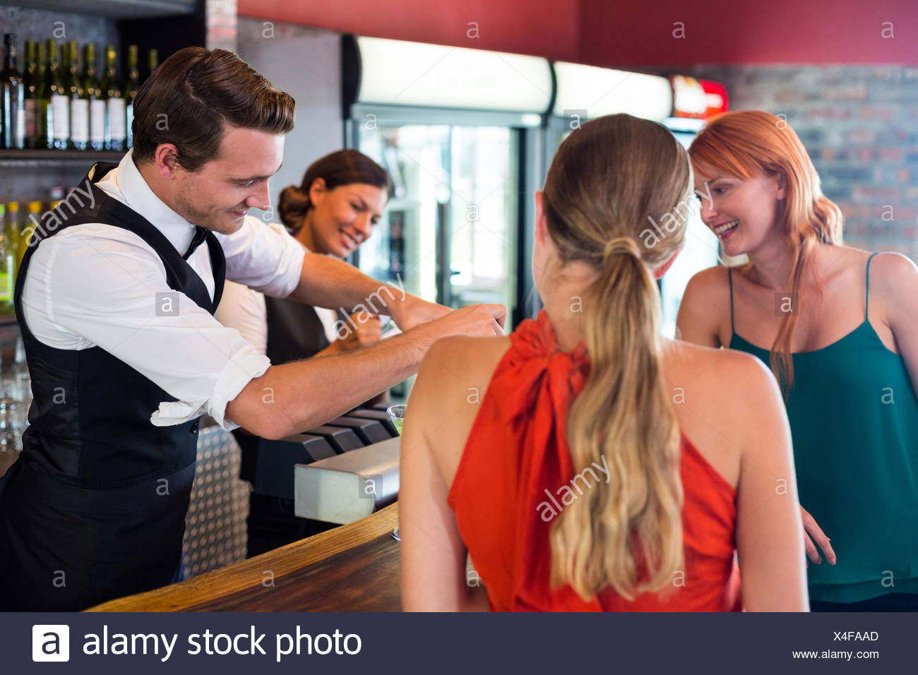 Friends standing at counter while bartender preparing a drink - Stock Image