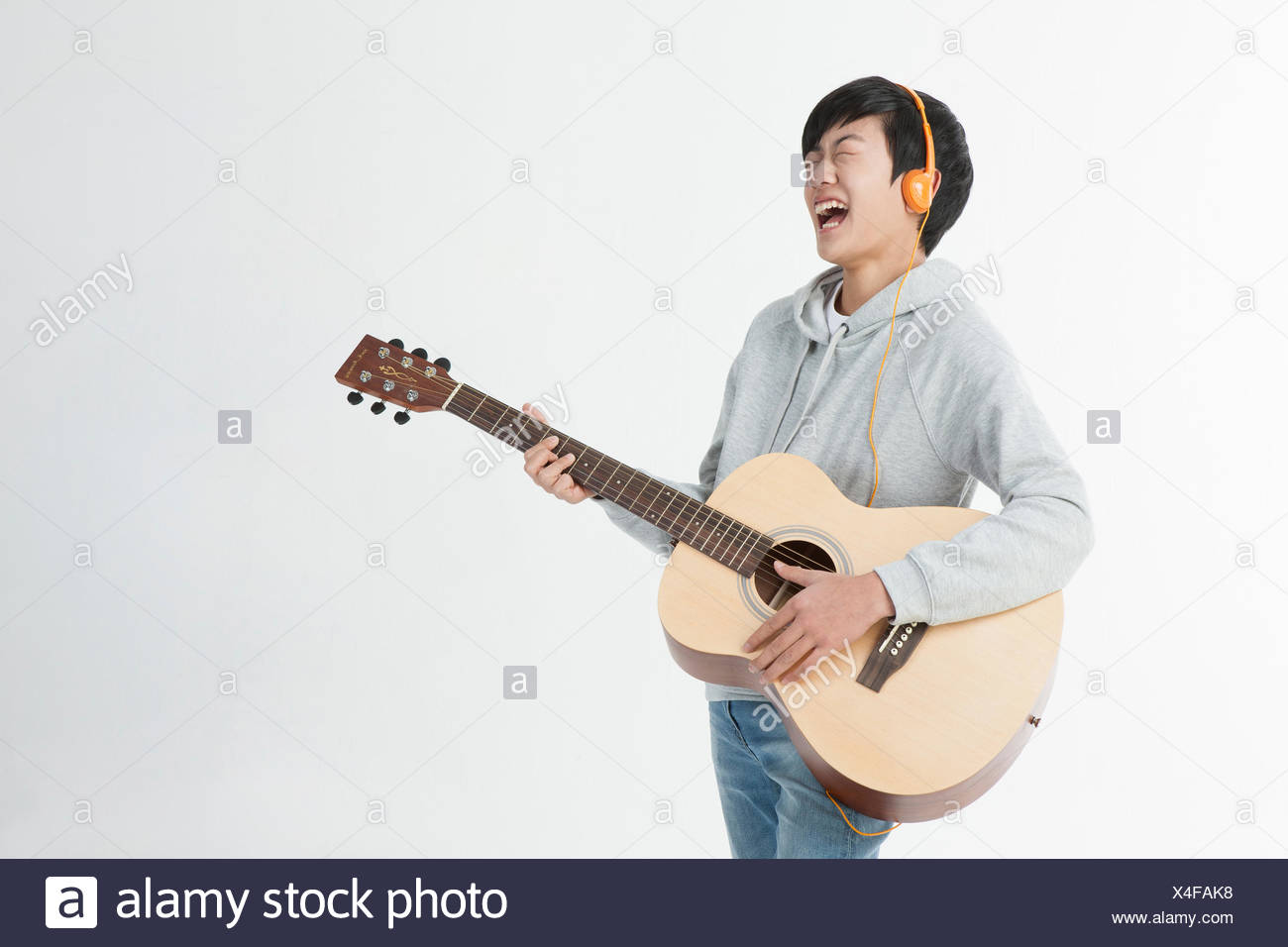 Side view of smiling school boy playing a guitar closing his eyes - Stock Image